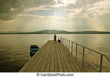 the girl  silhouette over the lake background