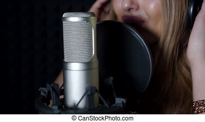 The girl sings into the microphone.