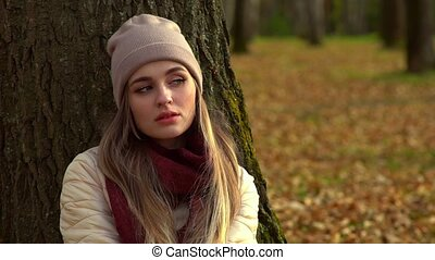 The girl sits alone in the autumn Park, on the ground under a tree.