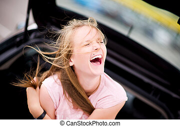 the girl sits in the car on a summer day and laughs out loud, squinting her eyes. Warm positive weekend
