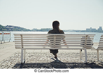 The girl sits on a bench by the river and enjoys a beautiful sunset. Golden sunset on the lake.