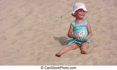 The girl sits on sand