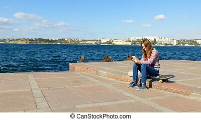 The girl sits on the quay and makes selfy. - Devoca sits on...