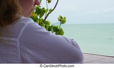 The girl sits on the terrace and looks towards the sea