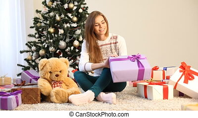 the girl sitting by the Christmas tree and gifts opens