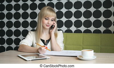 The girl sitting in a cafe talking on mobile phone