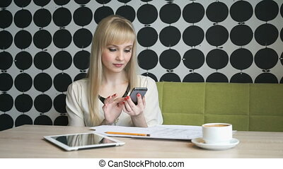 The girl sitting in a cafe texting friend