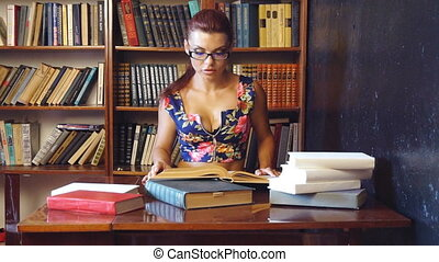 the girl sitting in the library reading books is preparing for exams