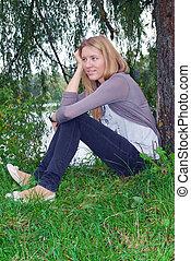 the girl sitting near willow near the lake.