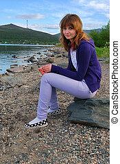 The girl sitting on coast