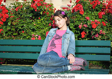 The girl sitting on the bench.