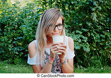 the girl sitting on the grass and drink coffee
