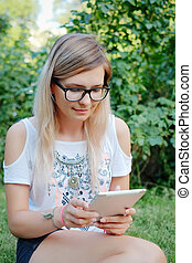 the girl sitting on the grass with tablet in hands