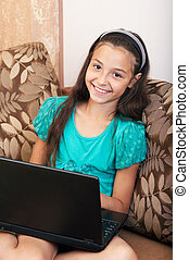 The girl sitting on the sofa with laptop