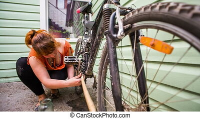 The girl smears a dirty and rusty bicycle star - The girl,...