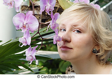 The girl smells an orchid