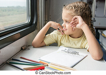 The girl smiled happily looking out the window drawing pencils in a train