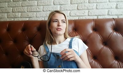 The girl speaks sitting on a leather sofa