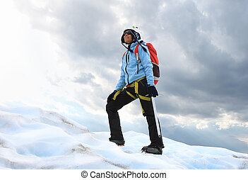 The girl standing on the icy top of glacier