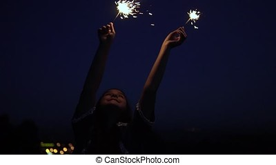 The girl stands against the background of the city at night and holds fireworks in her hands. slow motion.