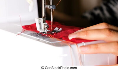 The girl starts sewing on a sewing machine
