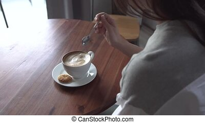 The girl stirs sugar in a Cup of coffee. Female hands closeup with cup coffee