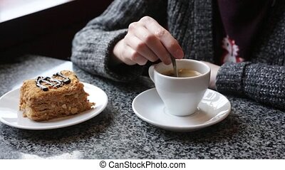 The girl stirs sugar in a white cup of coffee. Female hands with a cup of americano of espresso.