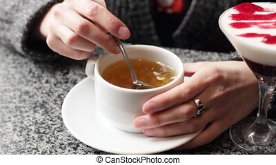 The girl stirs sugar in a white mug. Female hands closeup with a cup of tea.