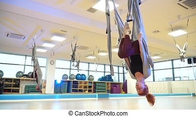 The girl swinging in a hammock to fly upside down yoga