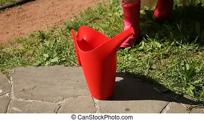 The girl takes a red watering can