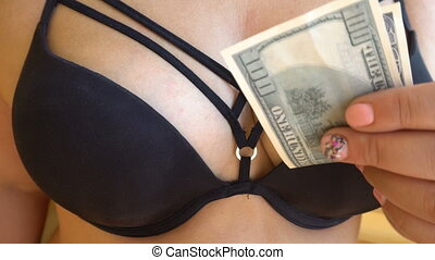 the girl takes dollar bills,put the money in a black bra in Striptease dancing