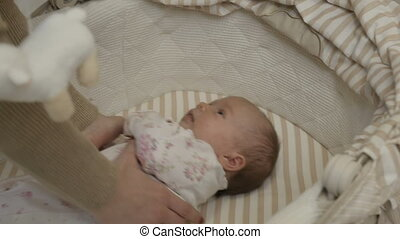 The girl takes the child out of the crib - Mom's hands close...