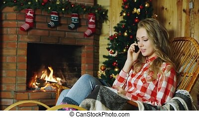 The girl talking on the phone at the fireplace
