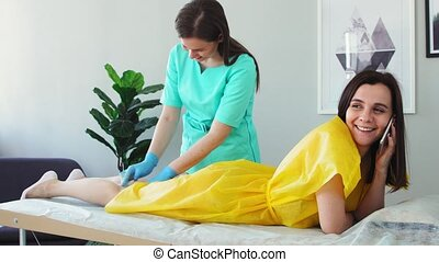 The girl talks on the phone and smiles during hair removal...