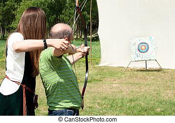 The girl teaches a man to archery