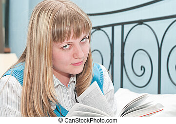 The girl the blonde reads the book lying on a bed