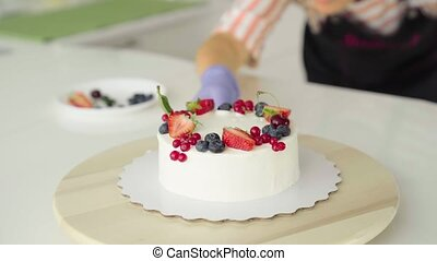 The girl, the chief confectioner, decorates forest berries, strawberries, a homemade cake