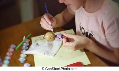 the girl the child paints a doll of manual work. girl...