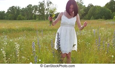 The girl the field collects wildflowers. Girl nature summer...