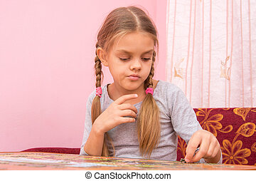 The girl thought collecting picture of puzzles