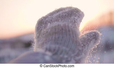 The girl throws snow with her palm. Hands close-up on sunset background