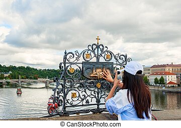 The girl touches the statue of St. John Nepomuk on Charles bridge Prague. The touch of a person to the memorial plaque of the Saint should bring good luck and ensure your well-being