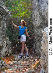 The girl tourist near to boulders on a mountain track. Rhodes. Greece.