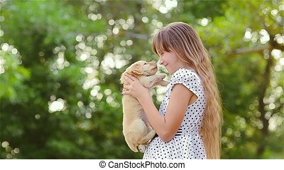 The girl turns a puppy on hands