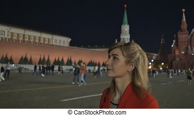 The girl walks and admires the night red square and the Kremlin in Moscow.
