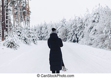 The girl walks and poses on the camera in the background of the winter forest