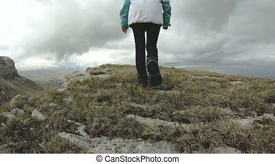 The girl walks in nature on a plateau next to a high cliff....