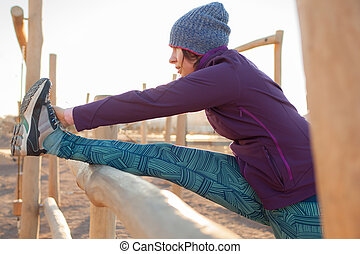 The girl warming up in the morning before jogging, stretching muscles of leg. Lead a healthy lifestyle