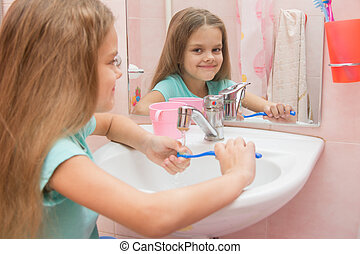 The girl washes a toothbrush under the tap