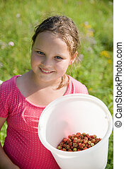 The girl with a bucket with a strawberry
